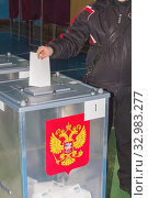 A young man votes at a polling station for the president of Russia. Стоковое фото, фотограф Акиньшин Владимир / Фотобанк Лори
