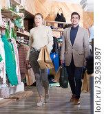 Купить «Couple is satisfied shopping and walking with package», фото № 32983897, снято 12 марта 2018 г. (c) Яков Филимонов / Фотобанк Лори