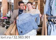 Купить «Young female with male are looking on jeans blouse for her», фото № 32983901, снято 12 марта 2018 г. (c) Яков Филимонов / Фотобанк Лори