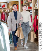 Купить «Young woman and man are walking satisfied with packadge after shopping», фото № 32983905, снято 12 марта 2018 г. (c) Яков Филимонов / Фотобанк Лори