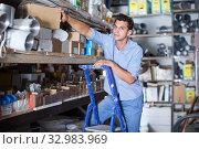Купить «sellerman s standing on the stairs near the shelves with boxes», фото № 32983969, снято 26 июля 2017 г. (c) Яков Филимонов / Фотобанк Лори