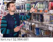 Handsome fisherman choosing fishing lures. Стоковое фото, фотограф Яков Филимонов / Фотобанк Лори