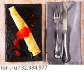 Купить «Roll of thin pancake with red caviar», фото № 32984977, снято 3 апреля 2020 г. (c) Яков Филимонов / Фотобанк Лори