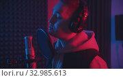 Купить «A man in headphones rapping through the pop-filter in the microphone - sound recording studio in neon lighting», видеоролик № 32985613, снято 3 июля 2020 г. (c) Константин Шишкин / Фотобанк Лори