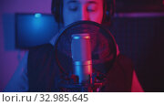 Купить «A man in hoodie rapping through the pop-filter in the microphone - recording his track in the studio», видеоролик № 32985645, снято 3 июля 2020 г. (c) Константин Шишкин / Фотобанк Лори