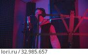 Купить «A man rapping through the pop-filter in the microphone - recording his track in the studio - music stand on the foreground», видеоролик № 32985657, снято 4 июля 2020 г. (c) Константин Шишкин / Фотобанк Лори