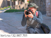 Купить «Portrait of a professional street and travel photographer with a camera pointed toward the subject», фото № 32987701, снято 2 апреля 2020 г. (c) easy Fotostock / Фотобанк Лори