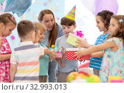 Купить «holidays, childhood and celebration concept - happy friends giving presents to birthday child at party in daycare», фото № 32993013, снято 27 мая 2020 г. (c) Оксана Кузьмина / Фотобанк Лори