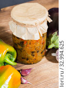 Homemade production canning, canned stewed vegetable puree caviar stewed with eggplant and pepper and garlic in a glass jar on a wooden background in a rustic style. Home provision. Стоковое фото, фотограф Светлана Евграфова / Фотобанк Лори