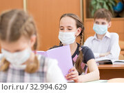 Купить «Pupils wearing protection mask to prevent virus during lesson in classroom», фото № 32994629, снято 24 мая 2020 г. (c) Оксана Кузьмина / Фотобанк Лори
