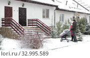 Купить «Caucasian loving couple coming to townhouse porch and entrance with baby stroller after waling. Strong snowfall at winter», видеоролик № 32995589, снято 21 января 2020 г. (c) Кекяляйнен Андрей / Фотобанк Лори