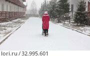 Woman in red jacket pushing baby carriage with small wheels on snowy pedestrian path in townhouse village, winter season. Стоковое видео, видеограф Кекяляйнен Андрей / Фотобанк Лори