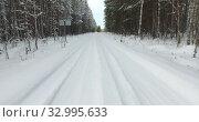 Купить «View at snowy road in winter forest, camera moving back. Snow covered forestry road with snowdrifts», видеоролик № 32995633, снято 20 января 2020 г. (c) Кекяляйнен Андрей / Фотобанк Лори