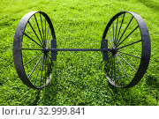Купить «Vintage black metal wheels on the grass», фото № 32999841, снято 8 сентября 2019 г. (c) EugeneSergeev / Фотобанк Лори