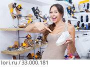 Купить «Laughing young woman standing with chosen shoe», фото № 33000181, снято 19 февраля 2020 г. (c) Яков Филимонов / Фотобанк Лори