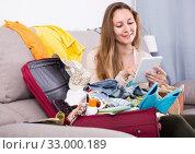 Купить «Girl choosing the hotel on the internet at home», фото № 33000189, снято 21 марта 2017 г. (c) Яков Филимонов / Фотобанк Лори
