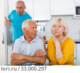 Upset man and woman quarrelling at home, son on background. Стоковое фото, фотограф Яков Филимонов / Фотобанк Лори