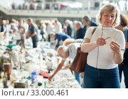 Man and woman choosing interesting souvenirs at traditional flea market. Стоковое фото, фотограф Яков Филимонов / Фотобанк Лори