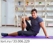 Купить «Young man exercising at home in sports and healthy lifestyle con», фото № 33006229, снято 3 мая 2017 г. (c) Elnur / Фотобанк Лори