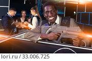 Afro businessman playing laser tag. Стоковое фото, фотограф Яков Филимонов / Фотобанк Лори