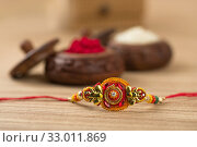Купить «Indian festival: Raksha Bandhan background with an elegant Rakhi, Rice Grains and Kumkum. A traditional Indian wrist band which is a symbol of love between Brothers and Sisters.», фото № 33011869, снято 27 июля 2018 г. (c) easy Fotostock / Фотобанк Лори