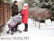 Купить «Loving couple with baby carriage holding hands while standing backyard at strong snowfall», фото № 33012757, снято 4 января 2020 г. (c) Кекяляйнен Андрей / Фотобанк Лори