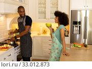 Купить «Happy young couple cooking and wearing apron in the kitchen», фото № 33012873, снято 28 ноября 2019 г. (c) Wavebreak Media / Фотобанк Лори