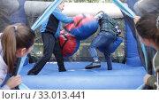 Купить «Two men in big boxing gloves boxing on inflatable ring in outdoor amusement park», видеоролик № 33013441, снято 12 ноября 2019 г. (c) Яков Филимонов / Фотобанк Лори