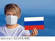 Купить «Woman in surgical face mask holds Russian flag confirmed infected people», фото № 33014445, снято 26 января 2020 г. (c) Kira_Yan / Фотобанк Лори
