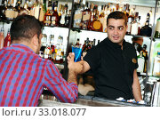 Купить «Barman worker serving cocktail to bar client», фото № 33018077, снято 15 сентября 2015 г. (c) Дмитрий Калиновский / Фотобанк Лори