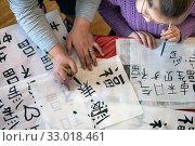 Учитель показывает девочке, как писать китайские иероглифы на уроке калиграфии в городе Москве, Россия. Редакционное фото, фотограф Николай Винокуров / Фотобанк Лори