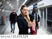 Купить «Female passenger with phone waiting for subway train», фото № 33018529, снято 3 июля 2020 г. (c) Яков Филимонов / Фотобанк Лори