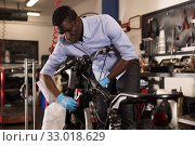 Confident afro american worker using his tools for repairing in motorcycle workshop. Стоковое фото, фотограф Яков Филимонов / Фотобанк Лори
