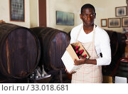 Positive afro seller working in wine store, holding box full of bottles with wine. Стоковое фото, фотограф Яков Филимонов / Фотобанк Лори