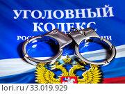 Наручники лежат на брошуре с Уголовным кодексом Российской Федерации (2020 год). Редакционное фото, фотограф Николай Винокуров / Фотобанк Лори