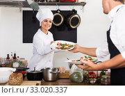 Happy woman cook giving salad to waitress. Стоковое фото, фотограф Яков Филимонов / Фотобанк Лори