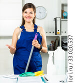 Купить «Young female cleaner in protective uniform at company office», фото № 33020537, снято 4 июня 2019 г. (c) Яков Филимонов / Фотобанк Лори