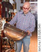 Купить «Glad man carefully examining antiques», фото № 33020541, снято 15 мая 2018 г. (c) Яков Филимонов / Фотобанк Лори