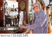 Купить «man visiting shop of antique goods», фото № 33020545, снято 15 мая 2018 г. (c) Яков Филимонов / Фотобанк Лори