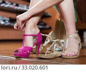Купить «Girl is trying on heeled sandals in shoes shop», фото № 33020601, снято 10 мая 2017 г. (c) Яков Филимонов / Фотобанк Лори