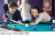 Купить «Positive smiling young couple playing pool in billiards», фото № 33020781, снято 16 марта 2016 г. (c) Татьяна Яцевич / Фотобанк Лори