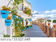 Idyllic scenery empty picturesque street of small white-washed village of Mijas. Path way decorated with hanging plants in bright blue flowerpots, Costa del Sol, Andalusia, Province of Málaga, Spain (2019 год). Стоковое фото, фотограф Alexander Tihonovs / Фотобанк Лори