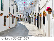 Купить «Mijas white washed street, small famous village in Spain. Charming empty narrow streets with New Year decorations, on houses walls hanging flower pots, sunny day no people. Costa del Sol, Málaga», фото № 33021657, снято 17 декабря 2019 г. (c) Alexander Tihonovs / Фотобанк Лори