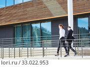 Zwei Geschäftsleute auf dem Weg zu einem Termin in Eile vor dem Bürogebäude. Стоковое фото, фотограф Zoonar.com/Robert Kneschke / age Fotostock / Фотобанк Лори