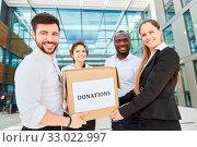 Business Team mit Karton mit einer Spende als karitative Unternehmensspende. Стоковое фото, фотограф Zoonar.com/Robert Kneschke / age Fotostock / Фотобанк Лори