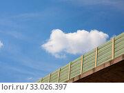 Купить «Laermschutzwand an einer Autobahnbruecke - Ausschnitt - Hintergrund blauer Himmel und weisse Wolke.», фото № 33026397, снято 2 июня 2020 г. (c) easy Fotostock / Фотобанк Лори