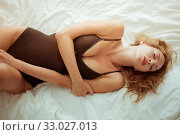 Купить «Beautiful sexy slim girl with a perfect figure lies on a white sheet in black bodysuit», фото № 33027013, снято 9 сентября 2017 г. (c) katalinks / Фотобанк Лори