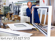 Man working in workshop for assembling plastic windows. Стоковое фото, фотограф Яков Филимонов / Фотобанк Лори
