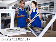 Foreman explaining plastic windows assembly process to young female worker. Стоковое фото, фотограф Яков Филимонов / Фотобанк Лори