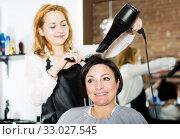 Купить «Hairdresser styling hair to adult woman», фото № 33027545, снято 7 марта 2017 г. (c) Яков Филимонов / Фотобанк Лори